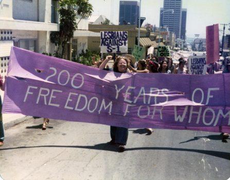 Marchers behind a banner challenging the Bicentennial, 1976