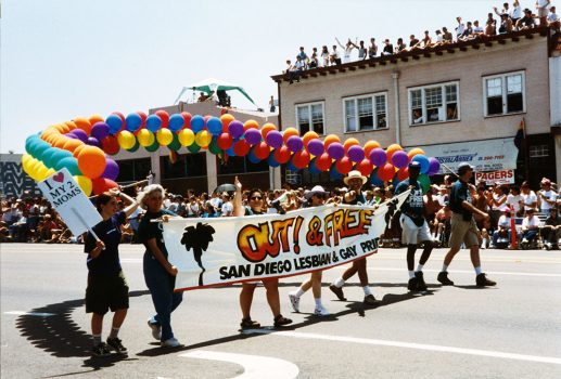 """Parade participants carrying """"Out & Free"""" banner and balloons, 1995"""