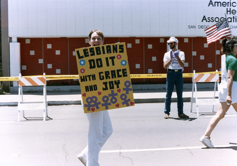Diane Germain with sign in Pride parade, 1988
