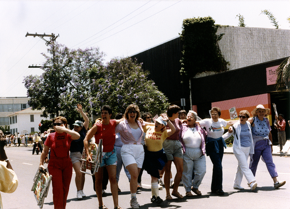 Women smile and wave in Pride parade, 1988